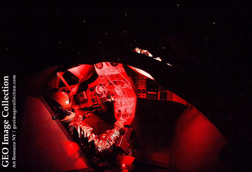 Time-exposure view of a pressure suited test subject inside a Gemini capsule.