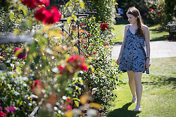 © Licensed to London News Pictures. 23/08/2016. Wisley, UK. Katie from Surrey admires the Jubilee Rose Garden in the afternoon sunshine at RHS Wisley. Photo credit: Peter Macdiarmid/LNP