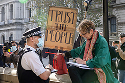 © Licensed to London News Pictures. 07/11/2020. London, UK. A police officer speaks with a woman opposite Downing Street during a small protest against new lockdown restrictions. New restrictions are now in force in England and pubs, restaurants, non-essential shops and gyms have closed. Photo credit: Rob Pinney/LNP