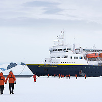 """A group of people walk across the fast ice in front of the National Geographic Explorer while """"parked"""" in Crystal Sound in Antarctica."""
