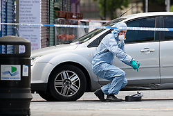 © Licensed to London News Pictures. 27/05/2019. London, UK.  A Police forensic officer taking fingerprint samples from a car at the crime scene in St Paul's Way, Mile End in Tower Hamlets, where a 23 year old man was stabbed multiple times yesterday, 26th May and died overnight in hospital.  Photo credit: Vickie Flores/LNP