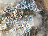 Aerial view over the clouds of traditional white houses on Santorini island, Greece.