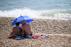 © Licensed to London News Pictures. 03/07/2018. Hove, UK. A couple shelter form the hot sun, underneath an umbrella, on the seafront at Hove, East Sussex on the south coast of England, as a heatwave continues across the UK. Photo credit: Ben Cawthra/LNP
