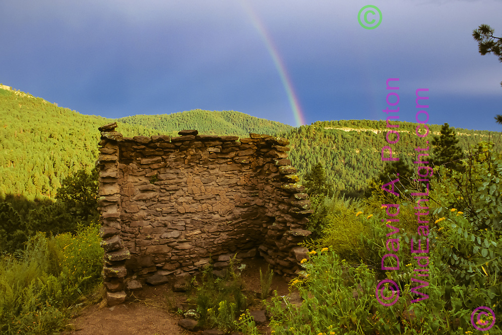 Standing walls of a singe room separated from the Sheshukwa Ruins of Ancestral Pueblo People on San Juan Mesa with a rainbow in the background, Santa Fe National Forest, Jemez Mountains, New Mexico, 8/29/1993. This structure was vandalized in the year 2000 or 2001, and the forest in the background was mostly destroyed in 2014 when the US Forest Service added prescription burning to the west side of the lightning-caused Pino Fire, resulting in devastating crown fire on the west side of Cerro Pino. © 1993, David A. Ponton