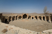 A disused caravanserai on the road from Yazd to Isfahan. The buildings served as a roadside inn for travellers. They provided security and each merchant stayed in one of the identical bays with the square used for animals. Iran, 2008