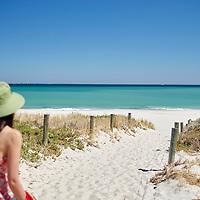 Sunsmart woman wearing a green hat walking to Leighton Beach