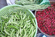 Fresh vegetables including snake beans and red chillies for sale at Daeum Kor morning market in Phnom Penh, the capital city of Cambodia. A large variety of local products are available for sale in fresh markets all over Cambodia, all being sold on small individual stalls.