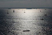 Small yachts and other boats sailing on a calm sea under blue sunny sky off the coast of Brittany on 26th September 2021 in Roscoff, Brittany, France. Brittany is a peninsula, historical county, and cultural area in the west of France. The surrounding seas are very popular for people with sail boats and larger yachting crews.