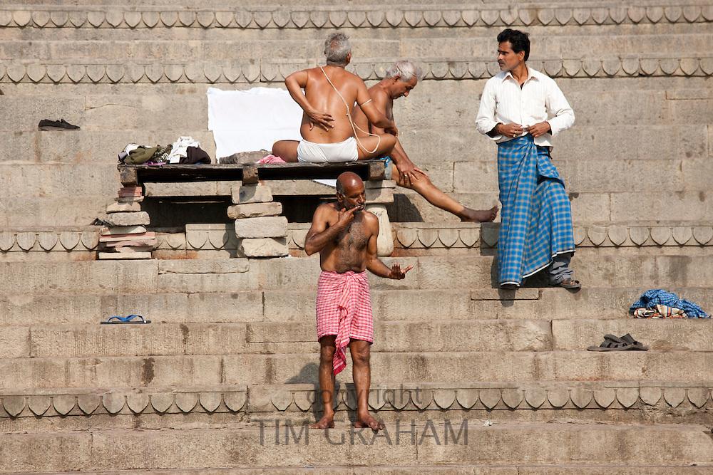 Men bathing at Dharbanga Ghat by the Ganges River in City of Varanasi, Benares, Northern India