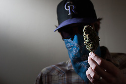 April 3, 2013 - Denver, Colorado, U.S. - 'WILLIAM BREATHES' holds up a marijuana bud at his office in Denver. Breathes started reviewing marijuana in 2008 shortly after it became legal for medicinal use in Colorado. He writes for Denver Westword and Tokeofthetown.com. (Credit Image: © Eric Bellamy/ZUMAPRESS.com)