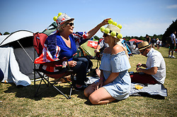 Karolin Lamb (left) repairs a hat belonging to her daughter Larissa, in the queue on day two of the Wimbledon Championships at the All England Lawn Tennis and Croquet Club, Wimbledon.