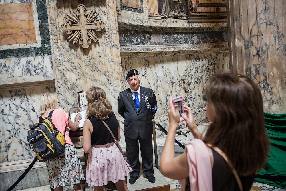 ROME, ITALY - 29 JULY 2014: Knight Pietro Rin, a Honor Guard to the royal tombs of the Pantheon, stands by the tomb of King Umberto I as tourists sign the guestbook and photograph, in Rome, Italy, on July 29th 2014.<br /> <br /> The National Institute for the Honor Guards to the royal tombs of the Pantheon is a monarchic-oriented whose goal is to watch over the royal tombs at the Pantheon. Italy's first king, Vittorio Emanuele II and his son Umberto I, as well as Umberto's wife Queen Margherita are entombed in the Pantheon.