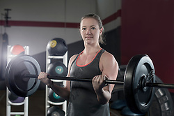 Young woman in the gym lifting barbell rod for bicep exercise, Bavaria, Germany