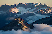 Jagged peaks emerge above the clouds at sunrise, as seen to the north from Klawatti Col, North Cascades National Park, Washington.