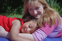 Teenage mother lying on picnic blanket in garden hugging young daughter,