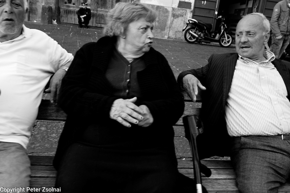 Elder people having conversation on a bench in Naples, Italy