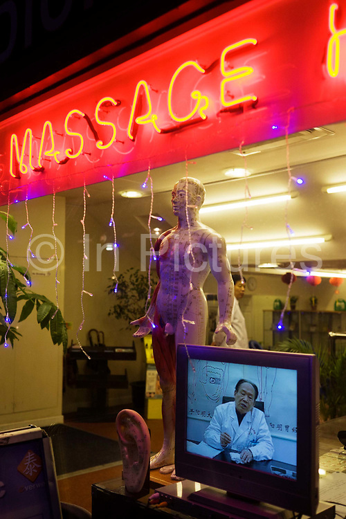 """A Doctor appears on a TV screen at a traditional Chinese herbalist's shop window in London's West End. There is also a real practitioner inside the shop. A model of the male body illustrating the meridians for acupuncture stands in the window alongside the TV and the word Massage is in red neon lights above the shop window. One of Chinese herbology's four natures is the degree of yin and yang, namely cold (extreme yin), cool, warm and hot (extreme yang). The patient's internal balance of yin and yang is taken into account when the herbs are selected. Medicinal herbs of """"hot"""", yang nature are used when the person is thought to be suffering from internal cold that requires to be purged, or when the patient is believed to have a general cold constituency. Sometimes an ingredient is added to offset the extreme effect of one herb."""