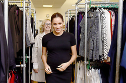 The Duchess of Sussex, walks through racks of clothes with Lady Juliet Hughes-Hallett, during her visit to Smart Works, in London, on the day that she has become their patron, as well as patron of the National Theatre, the Association of Commonwealth Universities, and the animal welfare charity, Mayhew.