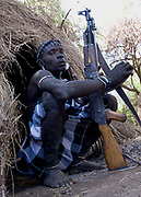 Young man with gun AK47, Mursi Tribe, Mago National Park, Lower Omo Valley, Ethiopia, portrait, person, one, tribes, tribal, indigenous, peoples, Southern, ethnic, rural, local, traditional, culture, primitive, Rifle, Weapon, Assault, hut, Kalashnikov