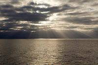 Rays of sun illuminate the surface of the open ocean.