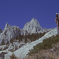 A mountaineer studies the east face of Mount Whitney, the highest summit in the lower 48 States, en route to climbing nearby mountains.