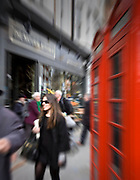 Girl in sunglasses walking by red telephone box in marylebone high street in london