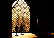 Silhouettes of women walking in front of the controverial pyramid by Architect I. M. Pei, at The Louvre Palace museum in Paris, France. September 1993