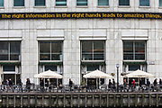 """""""The right information in the right hands leads to amazing things"""" written on the ticker on the Reuters building above an All Bar One restaurant in Canary Wharf, London, England, Unite Kingdom.  City workers walk past the building on a path next to the River Thames."""