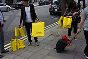 Shoppers carry their purchases in yellow Selfridges bags in London's West End. The bags are one of the capital's most striking symbols of British retail and are seen across the city as splashes of vibrant colour on the otherwise drab pavements and streets. The economic recovers appears to have begun in earnest and retail therapy has attracted these Londoners to the West End, away from the larger, warmer shopping Malls on the outskirts of town. Selfridges was founded by Harry Gordon Selfridge. The flagship store in London's Oxford Street is the second largest shop in the UK (after Harrods) and was opened on 15 March 1909.