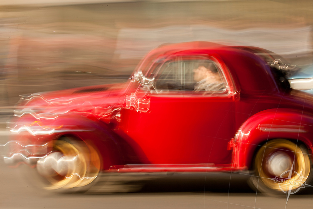 Speeding, red, compact car on the Streets of Rome, Italy