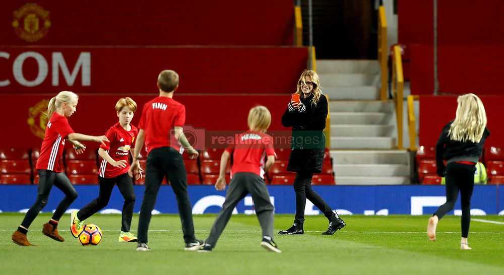 Julia Roberts takes photographs as her children Patricia, Phinnaeus and Henry play football on the pitch after the Premier League match at Old Trafford, London.