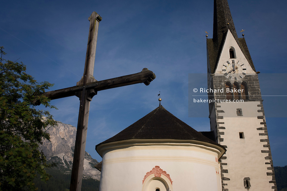 Typical Dolomites church architecture and cross in Leonhard-St Leonardo, a Dolomites village in south Tyrol, Italy.