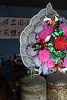 """China, Beijing, Chaoyang, San Jian Fang, 2008. A wreath usually reserved for funerals is displayed inside a restaurant protesting forcible eviction. The Chinese characters read: """"han wei guo jia"""" or """"protect country"""" and """"shi si wei hu"""" or """"pledge our lives.""""."""