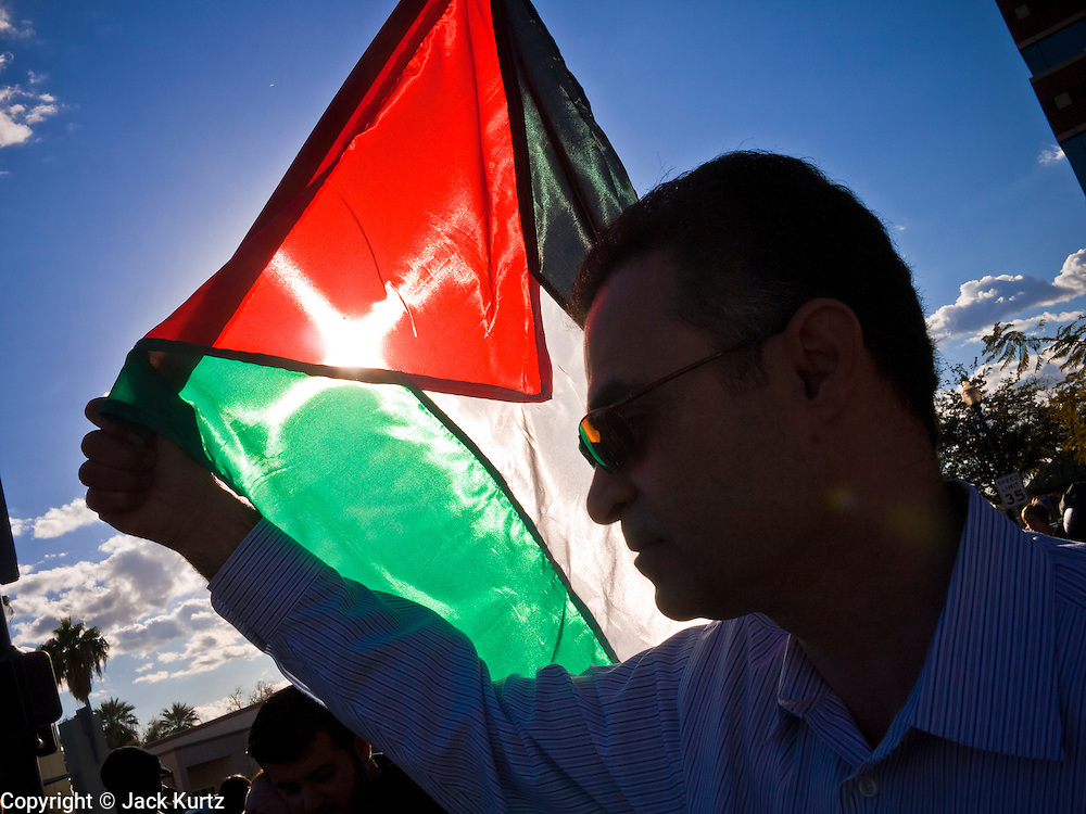 31 JANUARY 2011 - TEMPE, AZ: A man carries a Palestinian flag through Tempe, AZ, Monday. About 200 people marched through central Tempe, AZ, near the Arizona State University campus Monday afternoon. The rally was organized by the Arab American Association of Arizona in solidarity with the ongoing pro-democracy rallies and demonstrations in Egypt and other Arab countries.    Photo by Jack Kurtz