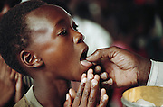A young boy takes a communion wafer during Sunday morning services at Regina Mundi Catholic Church service in Soweto, South Africa.