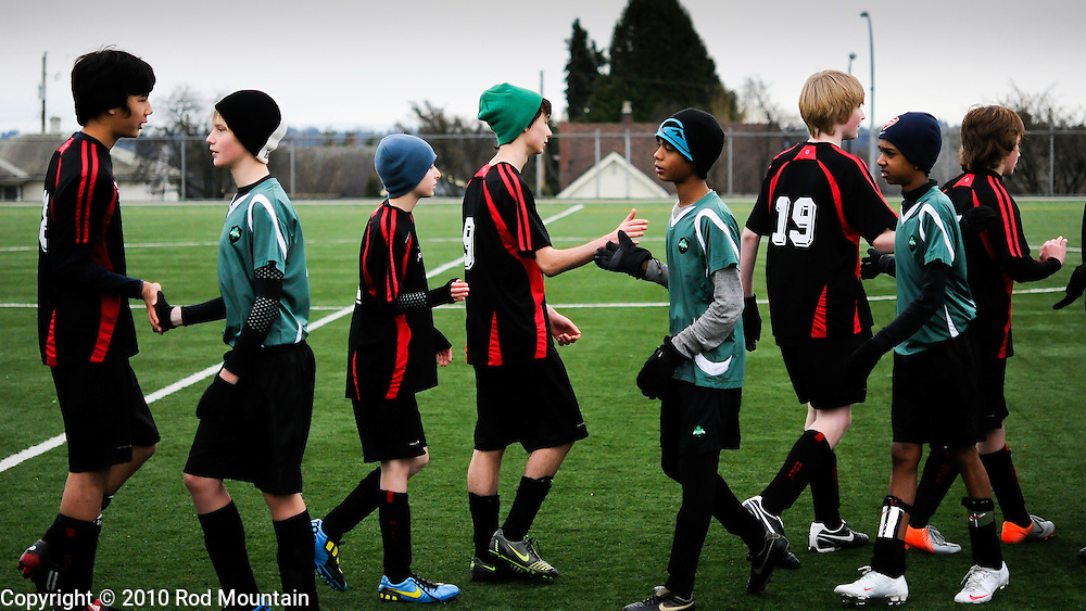 A group of boys lineup after the Soccer match to shake hands with the other team. Burnaby, British Columbia.<br /> <br /> Photo: © Rod Mountain