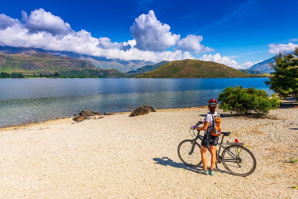 Cyclist on the shore of Lake Wanaka, Otago, South Island, New Zealand