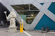An incongruous landscape of an imperial-style statue from the days of the Weimar Republic, with modern bikes and a tourist information dispenser at Humboldt Box in Berlin Mitte. The Humboldt-Box exhibition centre is a beloved tourist attraction in Berlin, glowing blue at the Museumsinsel, across from the Lustgarten and Berlin Cathedral. Visitors are drawn to the model of Berlin circa 1900.