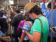 14 JULY 2011 - BANGKOK, THAILAND:   A man works on his iPad while riding the Sukhumvit line of the BTS Skytrain in Bangkok. The Bangkok Mass Transit System, commonly known as the BTS Skytrain, is an elevated rapid transit system in Bangkok, Thailand. It is operated by Bangkok Mass Transit System Public Company Limited (BTSC) under a concession granted by the Bangkok Metropolitan Administration (BMA). The system consists of twenty-three stations along two lines: the Sukhumvit line running northwards and eastwards, terminating at Mo Chit and On Nut respectively, and the Silom line which plies Silom and Sathon Roads, the Central Business District of Bangkok, terminating at the National Stadium and Wongwian Yai. The lines interchange at Siam Station and have a combined route distance of 55 km.    PHOTO BY JACK KURTZ