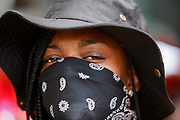 A black woman wears a mask while protesting against the KKK. Hundreds of counter protesters, including the Nation of Islam, New Black Panthers, and Huey Newton Gun Club, American Indian Movement, and ANTIFA gathered in downtown Dayton, Ohio to protest members of the Honorable Sacred Knights - a Ku Klux Klan group from Indiana. There were no arrests, and the protests ended peacefully as hundreds of police worked to keep the event peaceful and the protesters separated. Much of downtown Dayton was shutdown, and the courthouse square, where the KKK gathered, was surrounded by fence. Members of the KKK were given a police escort to the site, where about a dozen of them gathered, and then a police escort to safety.