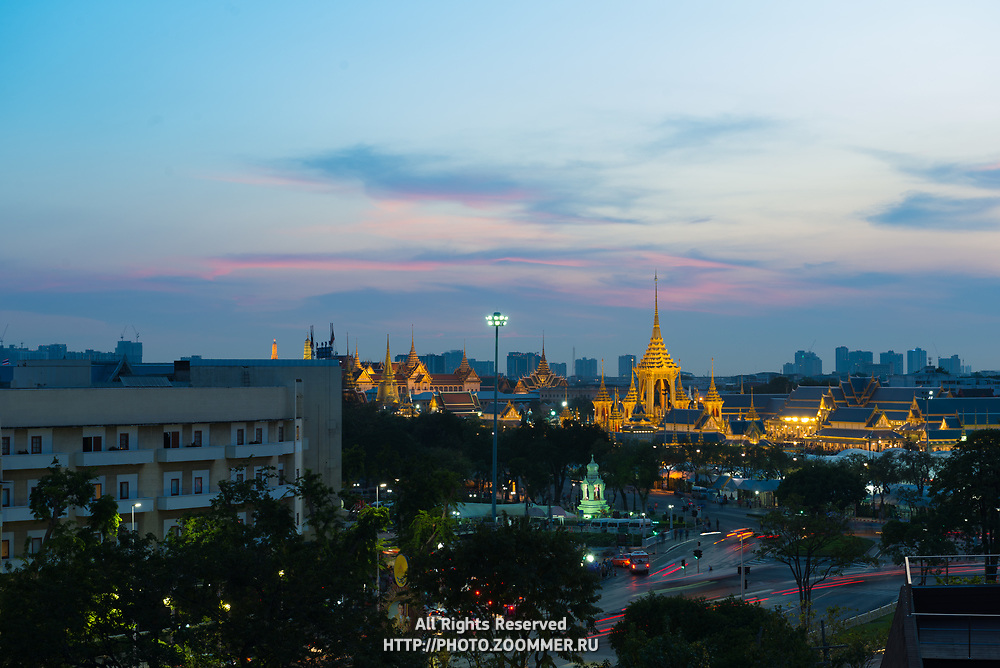 Bangkok panorama with traffic and buddist buildings at night from above
