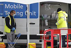 © Licensed to London News Pictures. 25/05/2021. London, UK. A completed Covid-19 test is taken from a driver at a mobile test site in a car park in Hounslow, west London. The government have advised against travel in eight areas in England, including the London borough of Housnlow, because of the rising number of Covid-19 infections due to the Indian variant of the disease. Photo credit: Peter Macdiarmid/LNP
