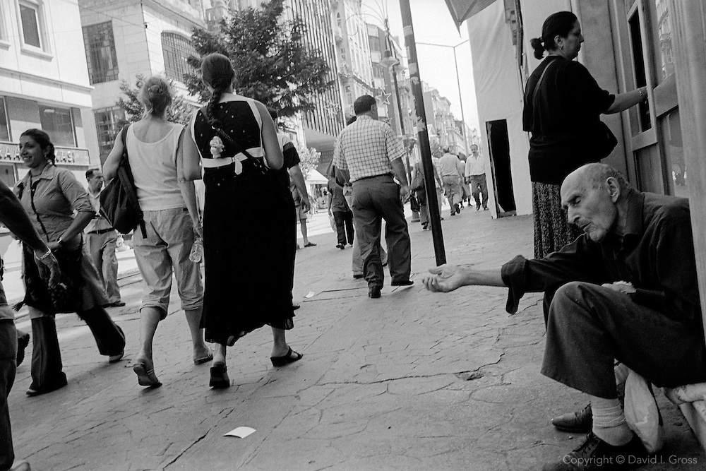A blind man begs for change on the main shopping street in the Beyoglu area of Istanbul.