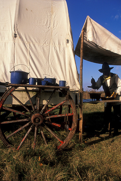 man preparing to cook using pots and pans sitting on a wagon wheel
