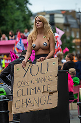 © Licensed to London News Pictures. 23/08/2021. LONDON, UK.  A topless climate activist from Extinction Rebellion on St Martin's Lane holds up a banner during a protest in Covent Garden.  The group has announced that it will stage protests in the capital for the next two weeks as they try to raise awareness of the effects of big business on climate change.  Photo credit: Stephen Chung/LNP