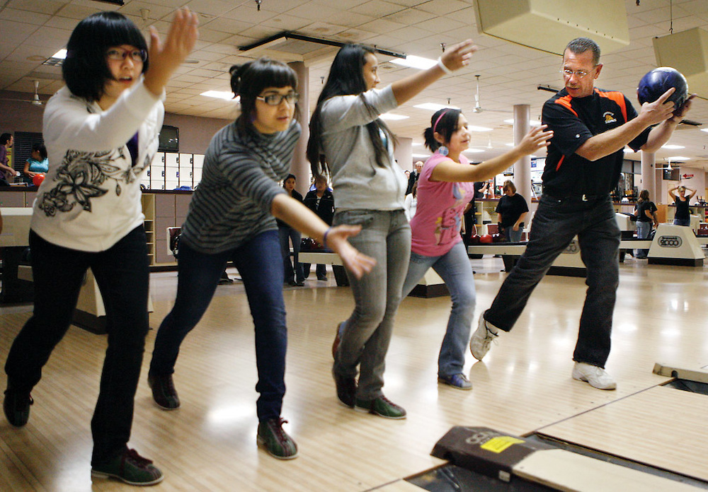 """Assistant coach Tom Richardson works with Xiao Yai, 18, left, Aliya Kamaletdinova, 17, Gabby Garcia, 15, and Xochitl Garcia, 16, during practice. """"We're trying to coach the girls to understand the principles and basics of bowling and adapt that to their own personal style,"""" says head coach Oscar Garnica. """"And the basics is just literally how to hold a bowling ball,"""" says Richardson. """"A lot of these girls literally don't know how to hold a bowling ball...we've literally taken girls from this season that were gutter to gutter -- they threw more gutters than they knocked down pins -- and worked them up to varsity this year."""""""