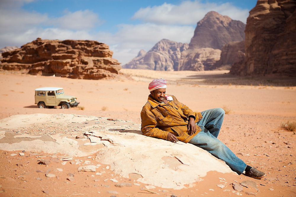 Sudanese Bedouin driver Ahmed relaxes near his jeep in the desert in Wadi Rum, Jordan.