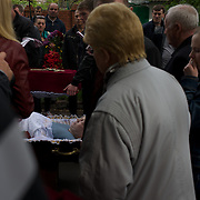 Family members pay respect to the body of Alexey Vorobyov, a bystander shot dead two days earlier during a gunfight between Ukrainian soldier and armed pro-Russia separatist groups in central Mariupol, eastern Ukraine.