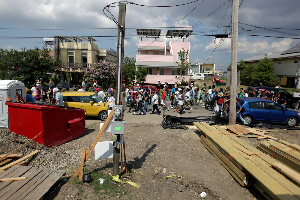 29 August 2015. Lower 9th Ward, New Orleans, Louisiana.<br /> Hurricane Katrina 10th anniversary memorials.<br /> A second line passes down Tennessee Street in front of Brad Pitt inspired make it Right homes and those yet to be built. <br /> Photo credit©; Charlie Varley/varleypix.com.