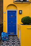 Yellow house with blue door and blue recycling bags on front doorstep, London. The bright complimentary colours seem over saturatedon such a grey day in the capital. By coincidence, the blue council recycling bags matches the blue door in a scene of domestic colour and residential landscape.